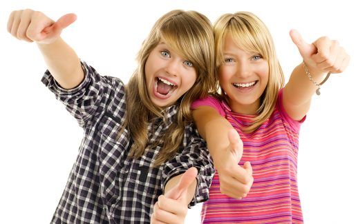 Portrait of happy teen girls showing thumbs up isolated one white